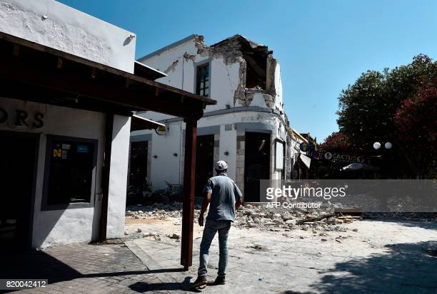 A pedestrian looks at the ruins of a bar on the island of Kos on July 21 where two patrons are said to have died following a 65 magnitude earthquake...