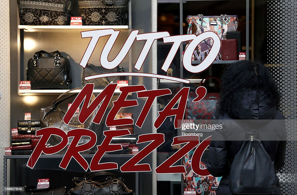 A pedestrian looks at the window display of a store advertising a half-price sale in Milan, Italy, on Thursday, Jan. 17, 2013. The euro-area economy won't return to growth until the next quarter as a recovery in Italy is delayed and France continues to shrink, according to a survey of economists. Photographer: Alessia Pierdomenico/Bloomberg via Getty Images
