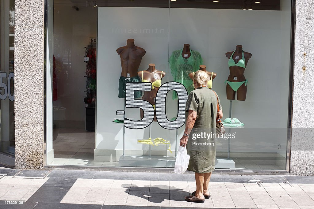 A pedestrian looks at the window display of a store offering a half price sale on swimwear and beach clothes in Pescara, Italy, on Thursday, Aug. 29, 2013. Italian consumer confidence rose this month more than economists expected as households grew optimistic amid expectations that the government would cut a property tax. Photographer: Marc Hill/Bloomberg via Getty Images