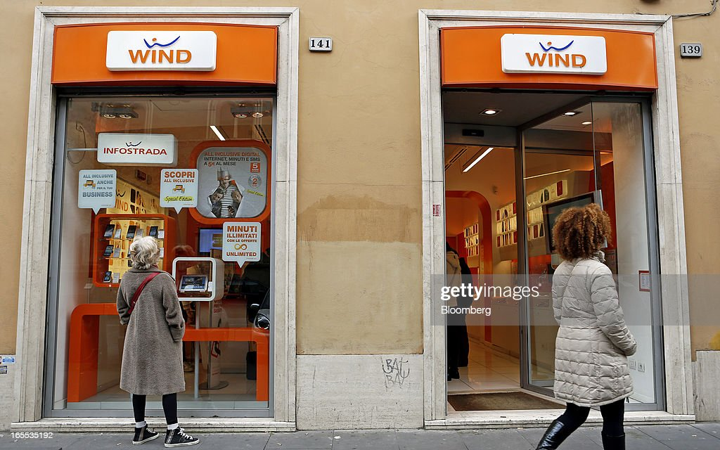 A pedestrian looks at the window display of a Wind SpA mobile phone store, owned by VimpelCom Ltd., in Rome, Italy, on Thursday, April 4, 2013. Italy's state-owned postal service and Wind SpA, the country's third-largest mobile-phone company, are discussing a possible venture with Wind's fixed-line network Infostrada, Poste Italiane SpA Chief Executive Officer Massimo Sarmi said. Photographer: Alessia Pierdomenico/Bloomberg via Getty Images