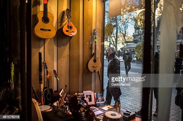 A pedestrian looks at the window display of Musical Emporium store during its last day open to the public on January 5 2015 in Barcelona Spain...