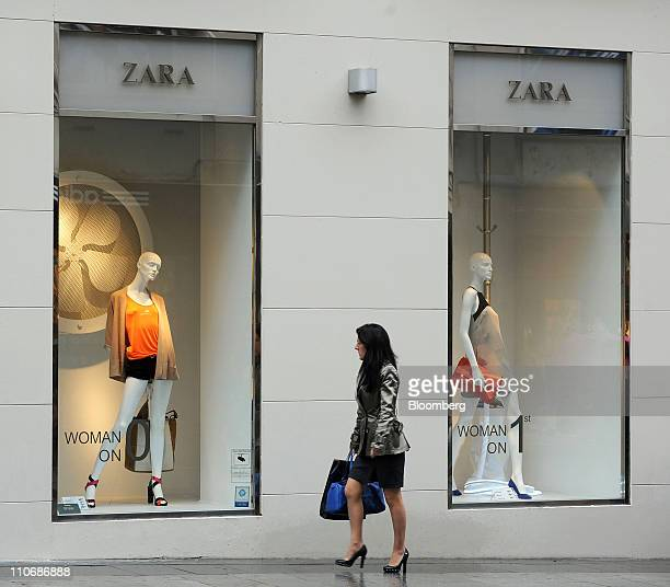 A pedestrian looks at the window displays of a Zara fashion store in Madrid Spain on Wednesday March 23 2011 Inditex SA owner of the Zara chain...
