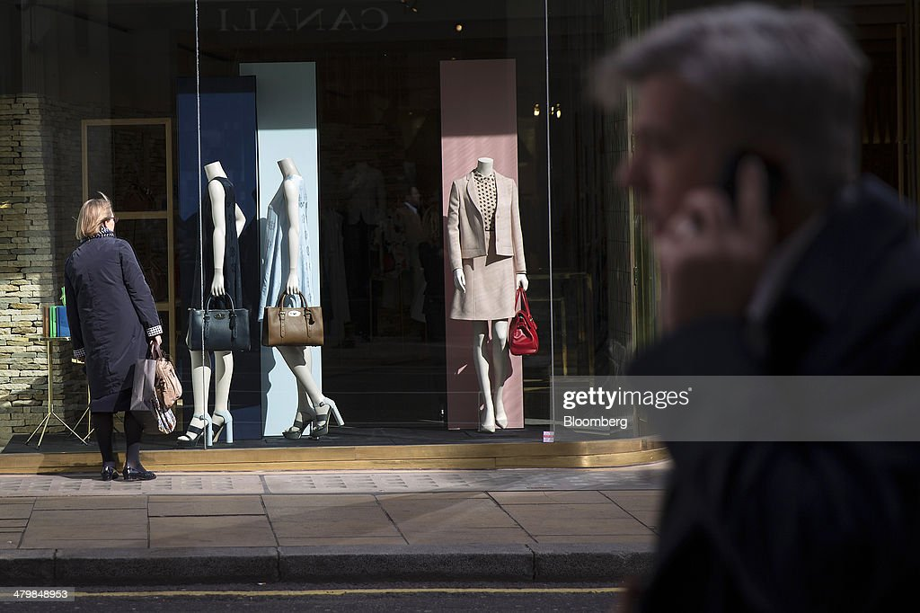 A pedestrian looks at women's clothing and accessories in the window display of a Mulberry Group Plc luxury store on New Bond Street in London, U.K., on Thursday, March 20, 2014. Mulberry Group said Bruno Guillon will step down as chief executive officer after two years during which the British luxury handbag maker lost two-thirds of its market value. Photographer: Simon Dawson/Bloomberg via Getty Images