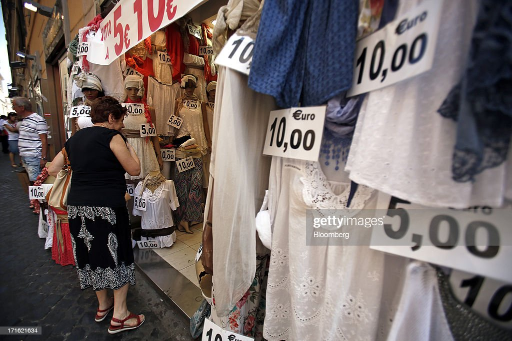 A pedestrian looks at women's garments displayed for sale at a discount clothes store in Rome, Italy, on Wednesday, June 26, 2013. Italian household confidence rose this month as consumers grew optimistic about the country's outlook as Prime Minister Enrico Letta's government plans to cut taxes and boost youth employment. Photographer: Alessia Pierdomenico/Bloomberg via Getty Images