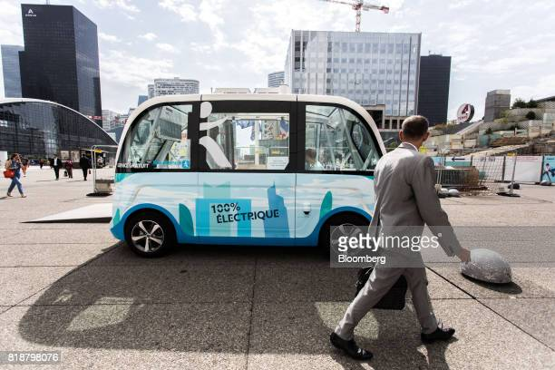A pedestrian looks on as an Arma autonomous shuttle bus manufactured by Navya Technologies SAS in La Defense business district of Paris France on...