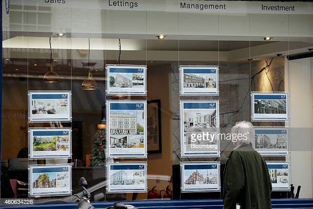 A pedestrian looks property information leaflets for luxury homes displayed in the window of an estate agent in the Knightsbridge district of London...