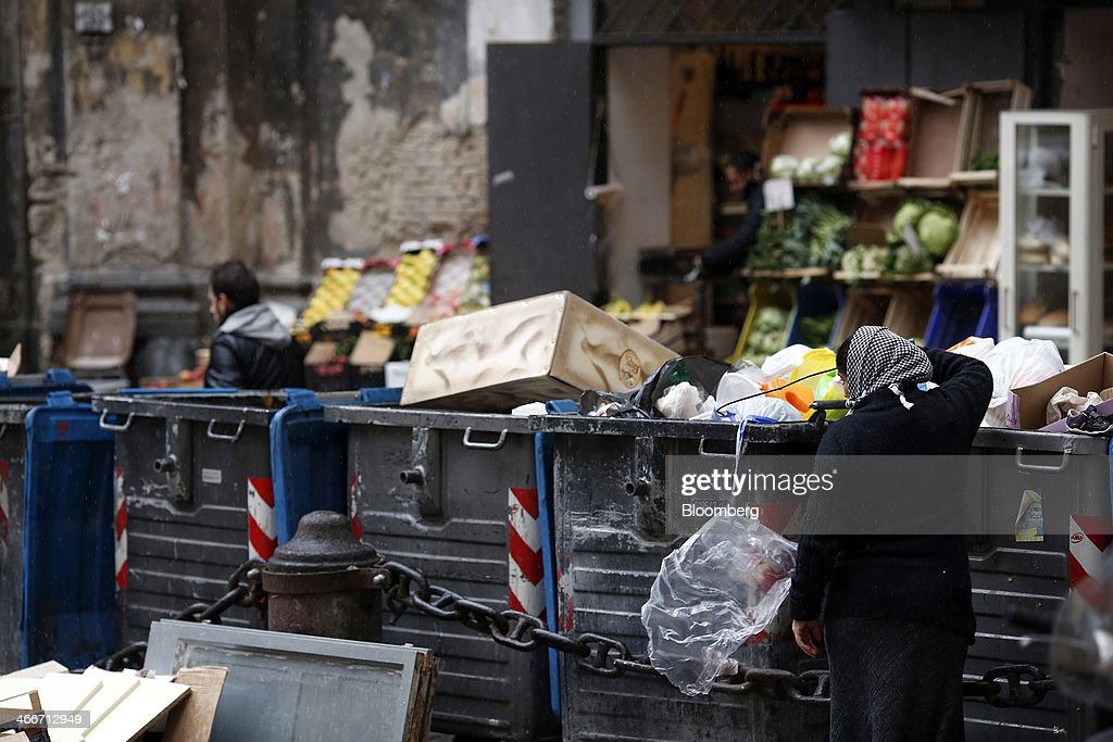 A pedestrian looks through garbage inside a trash can outside a store in Naples, Italy, on Saturday, Feb. 1, 2014. In Naples, the local youth unemployment rate in 2012 was 53.6 percent compared to a national average of 35.3 percent. Photographer: Alessia Pierdomenico/Bloomberg via Getty Images