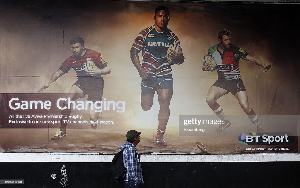 A pedestrian looks up at rugby players on a billboard advertisement for BT Group Plc's new sports television service BT Sport in London, U.K. on Friday, May 17, 2013. BT Group Plc said it will offer its new BT Sport channels free with broadband subscriptions to make its bundles of phone, Internet and TV service more appealing. Photographer: Simon Dawson/Bloomberg via Getty Images