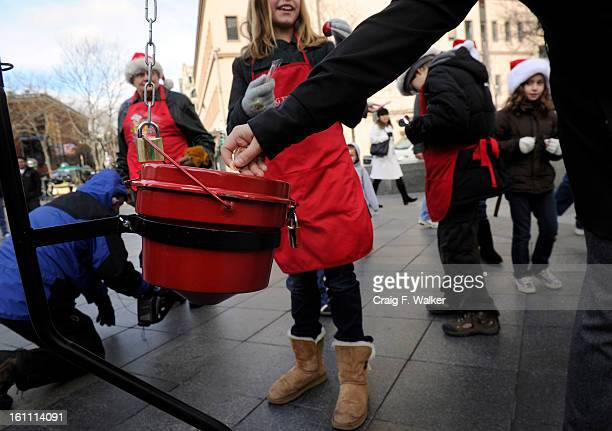A pedestrian makes a donation to the red kettle on the 16th Street Mall where Salvation Army Bell Ringer Merrill Fie is joined by his grandchildren...