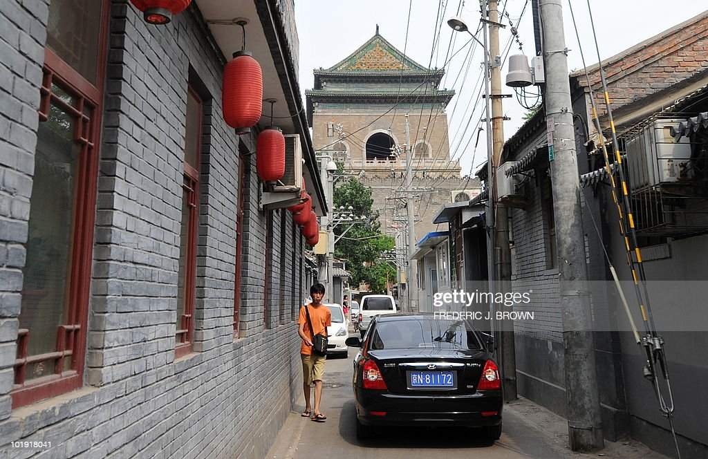 A pedestrian makes way for passing vehicles driving through a narrow hutong or traditional alleyway near central Beijing's ancient Drum and Bell...