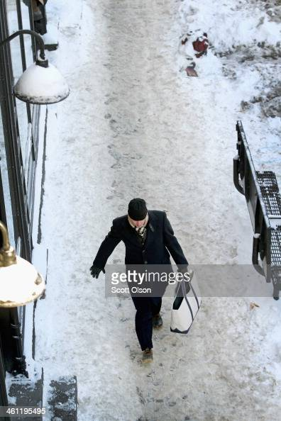 A pedestrian navigates a frozen sidewalk in below zero temperatures on January 7 2014 in Chicago Illinois Chicago is experiencing its third...