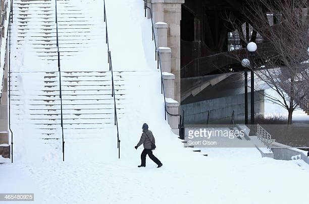 A pedestrian navigates a snowcovered stairway along the Chicago River as temperatures drop below zero January 27 2014 in Chicago Illinois The city is...