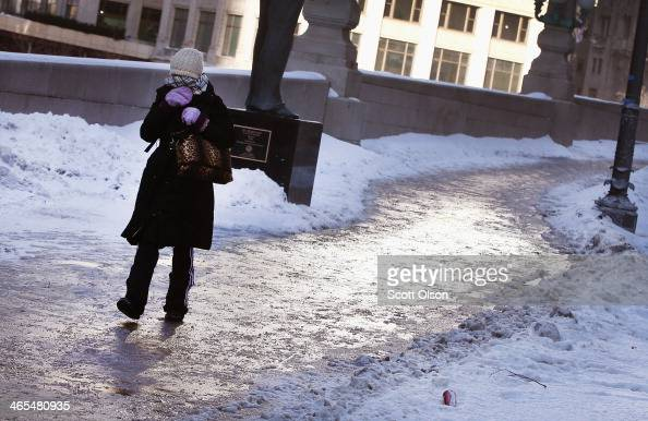 A pedestrian navigates an icecovered sidewalk along the Chicago River as temperatures drop below zero January 27 2014 in Chicago Illinois The city is...
