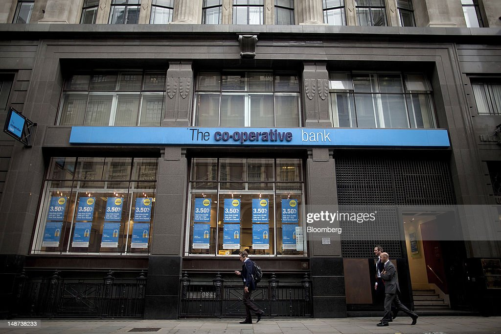 Pedestrian pass a Co-Operative Bank Plc branch in London, U.K., on Thursday, July 19, 2012. Lloyds Banking Group Plc agreed to sell 632 branches to Co-Operative Bank Plc for an initial 350 million pounds ($548 million), as the U.K.'s biggest mortgage lender divests assets to comply with its government bailout. Photographer: Simon Dawson/Bloomberg via Getty Images