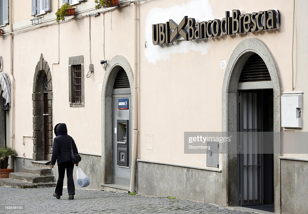 A pedestrian passes a Banco di Brescia bank branch, a subsidiary of Unione di Banche Italiane SCPA (UBI Banca), in Vetralla, Italy, on Monday, March 11, 2013. Intesa Sanpaolo SpA and UniCredit SpA are among Italian banks due to report losses for the fourth quarter this week, as the economic contraction meant more clients failed to repay their debts. Photographer: Alessia Pierdomenico/Bloomberg via Getty Images