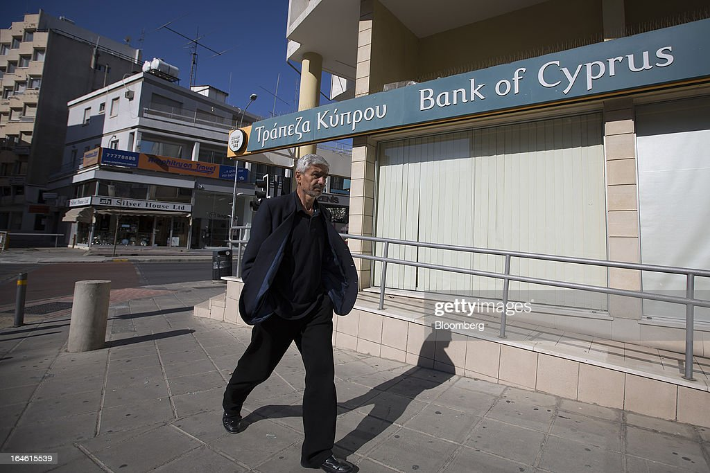 A pedestrian passes a Bank of Cyprus Plc branch in Nicosia, Cyprus, on Monday, March 25, 2013. Cyprus dodged a disorderly default and unprecedented exit from the euro by bowing to demands from creditors to shrink its banking system in exchange for 10 billion euros ($13 billion) of aid. Photographer: Simon Dawson/Bloomberg via Getty Images