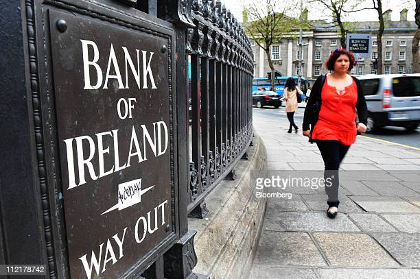 A pedestrian passes a Bank of Ireland automated sign outside a branch in Dublin Ireland on Thursday April 14 2011 Bank of Ireland Plc said it will...