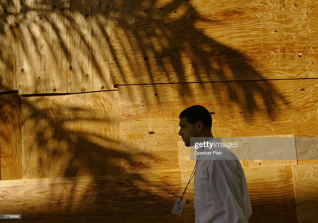 A pedestrian passes a boarded up store on the second day of the summit to create a Free Trade Area of the Americas (FTAA) November 18, 2003 in downtown Miami, Florida. Due to expected protests from anarchists, labor groups and globalization foes, much of the city of Miami is in a police lockdown, with thousands of businesses closed and a steel barricade circling the summit area.