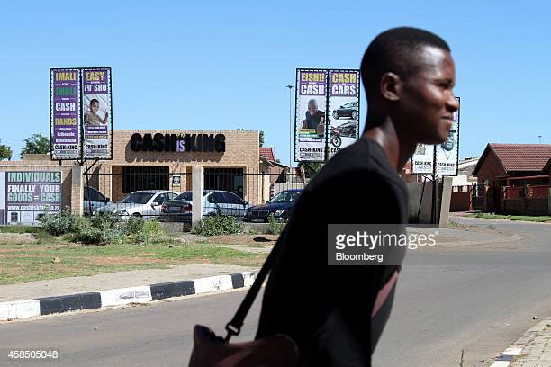 A pedestrian passes a Cash Is King loan shop in Soweto South Africa on Wednesday Nov 5 2014 Township economies have the potential to become an...