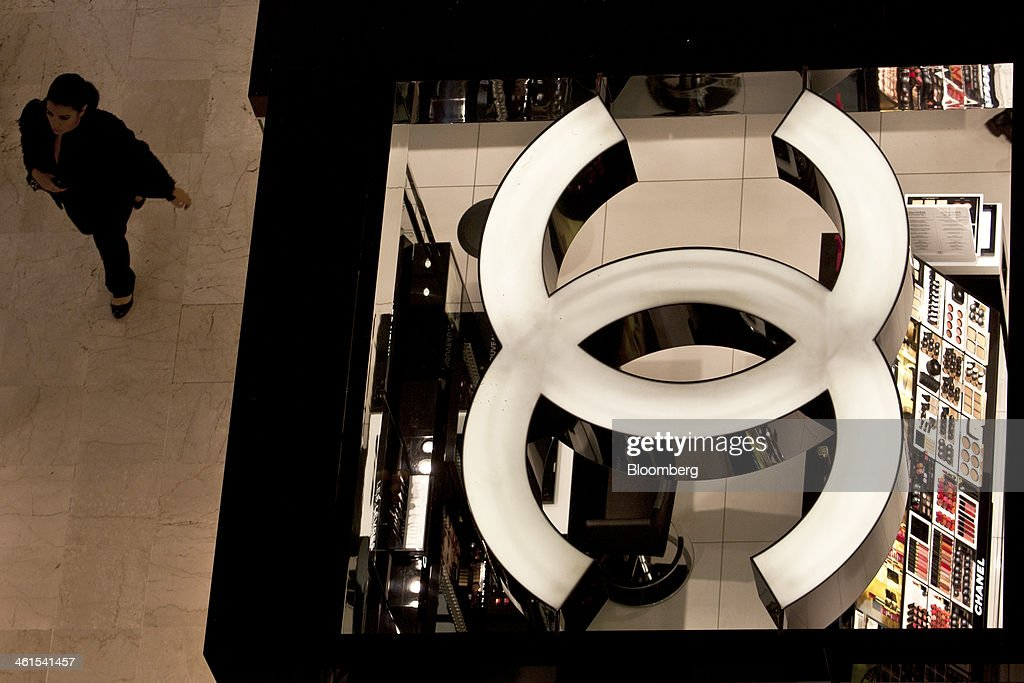 A pedestrian passes a Chanel SA sales stand as the luxury goods brand logo sits illuminated in the Galeries Lafayette SA luxury department store in Paris, France, on Wednesday, Jan. 8, 2014. France's trade deficit continues to widen, as high payroll taxes and inflexible labor rules price French-made goods out of the market. Photographer: Balint Porneczi/Bloomberg via Getty Images