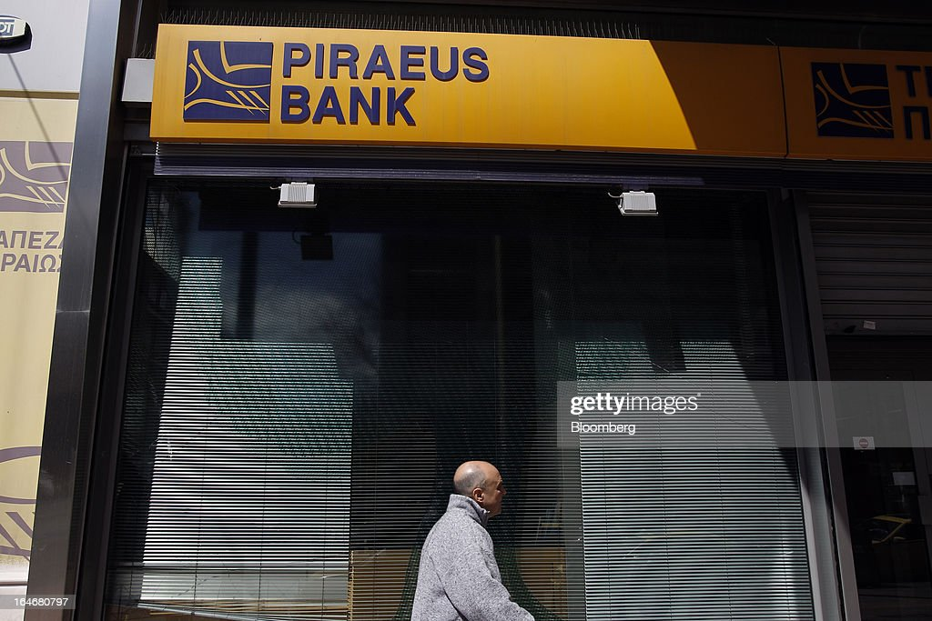 A pedestrian passes a closed branch of Piraeus Bank SA in Athens, Greece, on Tuesday, March 26, 2013. Piraeus Bank SA acquires Greek units of Cypriot lenders for total cash consideration of EU524m, according to e-mailed statement from the Athens-based lender today. Photographer: Kostas Tsironis/Bloomberg via Getty Images