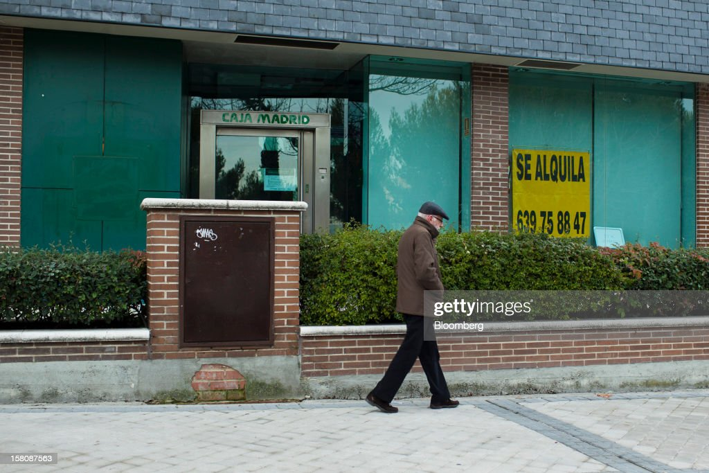 A pedestrian passes a closed down branch of Caja Madrid, part of the Bankia Group, in the wealthy Pozuelo de Alarcon suburb of Madrid, Spain, on Monday, Dec. 10, 2012. The jobless rate in Spain stands at 26 percent, jostling with Greece for the rank of highest on the continent. Photographer: Photographer: Angel Navarrete/Bloomberg via Getty Images
