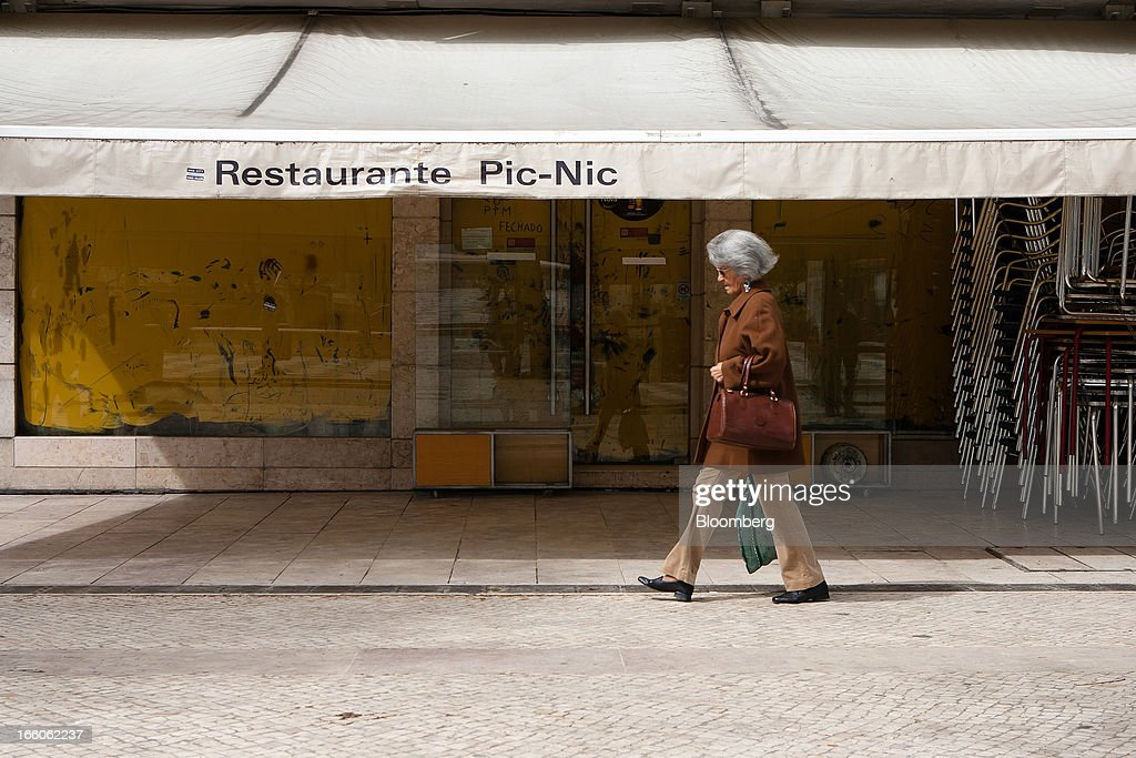 A pedestrian passes a closed down restaurant on Rossio plaza in Lisbon, Portugal, on Monday, April 8, 2013. Portugal will carry out more spending cuts this year after the Constitutional Court blocked a plan to suspend a monthly salary payment to state workers and pensioners. Photographer: Mario Proenca/Bloomberg via Getty Images