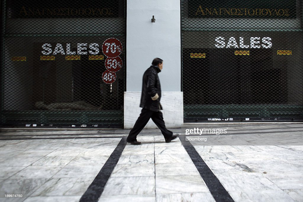 A pedestrian passes a closed store advertising sales discounts in its empty window displays in Athens, Greece, on Thursday, Jan. 24, 2013. Greece's government has implemented budget cuts and economic reforms to tame a fiscal deficit that has led to bailouts from the European Union and the International Monetary Fund. Photographer: Kostas Tsironis/Bloomberg via Getty Images