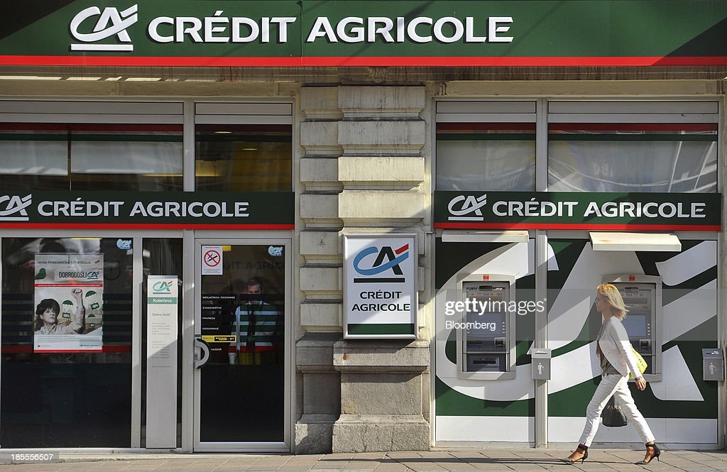A pedestrian passes a Credit Agricole SA bank branch in Belgrade, Serbia, on Monday, Oct. 21, 2013. Serbia's government revealed a salvo of measures to bring the public finance deficit and debt back under control by 2017 after the head of the largest coalition party warned the country was on the brink of insolvency. Photographer: Oliver Bunic/Bloomberg via Getty Images