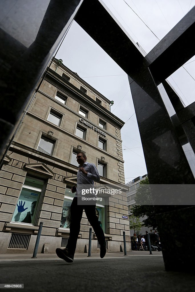 A pedestrian passes a Credit Suisse Group AG bank branch in Zurich, Switzerland, on Tuesday, May 6, 2014. Credit Suisse is close to resolving a U.S. tax-evasion probe with an agreement that might include a penalty of more than $1 billion, after creating a separate entity last year to house the businesses involved. Photographer: Philipp Schmidli/Bloomberg via Getty Images
