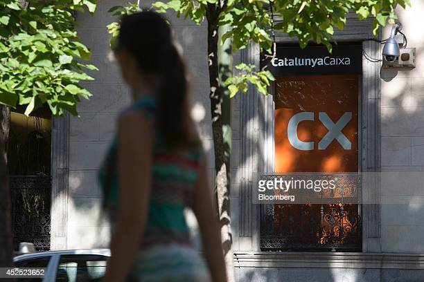 A pedestrian passes a 'CX' logo in a window at the headquarters of Catalunya Banc SA in Madrid Spain on Tuesday July 22 2014 Banco Bilbao Vizcaya...