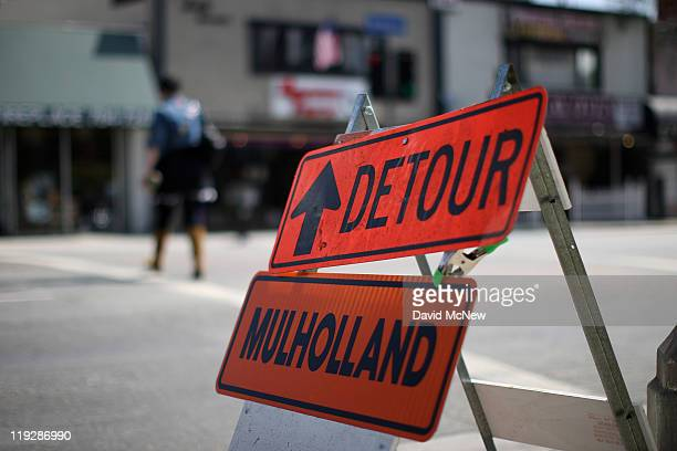 A pedestrian passes a detour sign as drivers heed the advice of widelypublicized warnings to stay off the roadways while workers demolish the south...