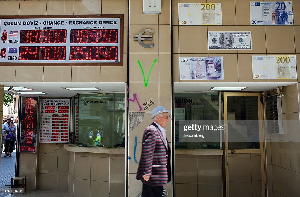 A pedestrian passes a digital display of euro and dollar currency rates outside an exchange bureau in Istanbul, Turkey, on Friday, June 7, 2013. The country's stocks and bonds have slumped this week as demonstrations spread nationwide after police used tear gas and water cannons on May 31 against demonstrators who had gathered in Gezi Park near Taksim to oppose plans to develop it. Photographer: Kerem Uzel/Bloomberg via Getty Images