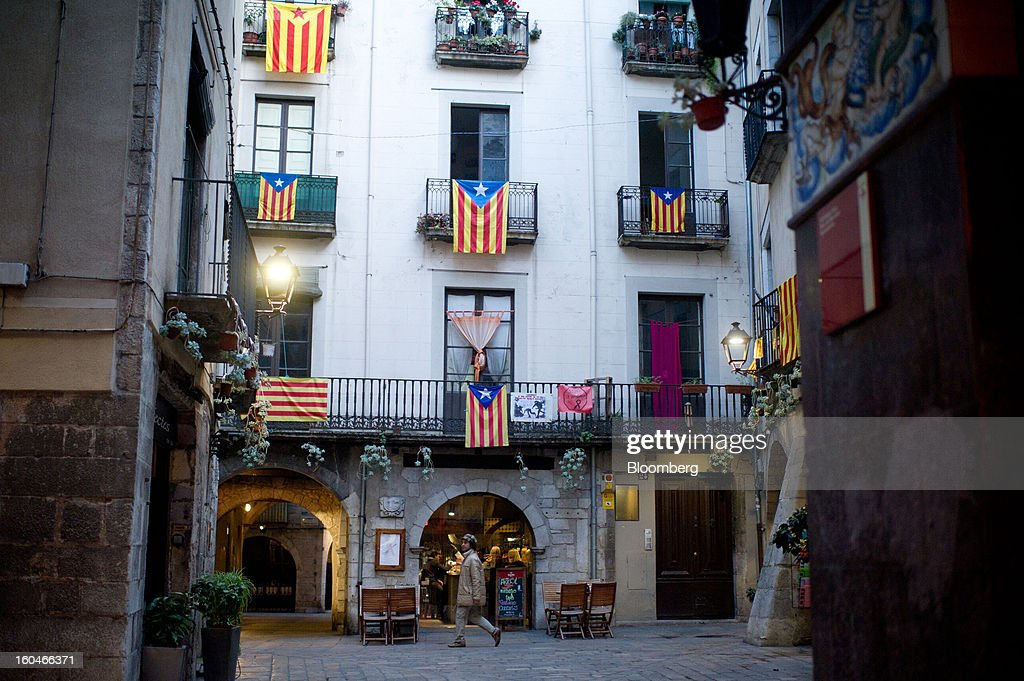 A pedestrian passes a display of pro-independence Catalan flags hanging from a building in Girona, Spain, on Thursday, Jan. 31, 2013. Spain's recession deepened more than economists forecast in the fourth quarter as the government's struggle to rein in the euro region's second-largest budget deficit weighed on domestic demand. Photographer: David Ramos/Bloomberg