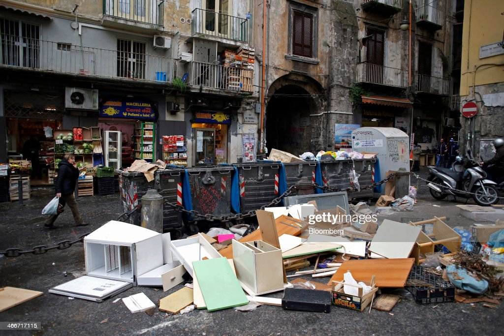 A pedestrian passes a disregarded white goods and furniture as she walks past garbage strewn around trash cans outside a store in Naples, Italy, on Saturday, Feb. 1, 2014. In Naples, the local youth unemployment rate in 2012 was 53.6 percent compared to a national average of 35.3 percent. Photographer: Alessia Pierdomenico/Bloomberg via Getty Images