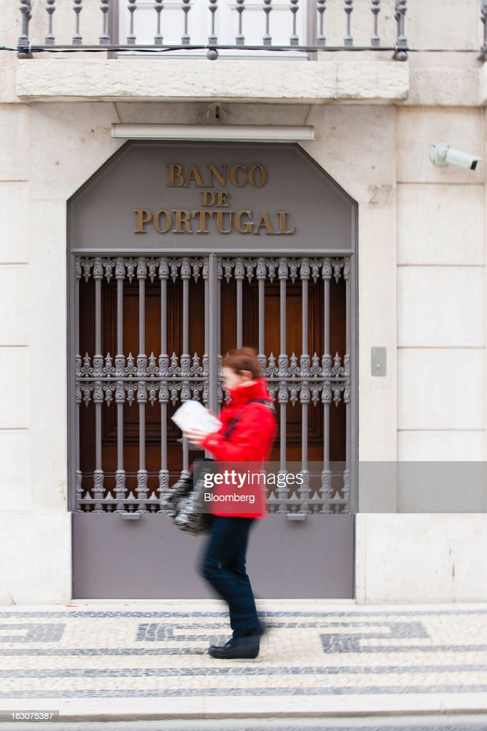 A pedestrian passes a doorway marked 'Banco de Portugal' outside the headquarters of the central bank in Lisbon, Portugal, on Saturday, March 2, 2013. Prime Minister Pedro Passos Coelho is battling rising joblessness and lower demand from European trading partners as he raises taxes to meet the terms of a 78 billion-euro ($104 billion) aid plan from the European Union and the International Monetary Fund. Photographer: Mario Proenca/Bloomberg via Getty Images