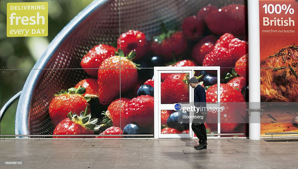 A pedestrian passes a giant poster advertising 'fresh' fruit outside a Tesco Plc supermarket in the borough of Kensington in London, U.K., on Tuesday, March 12, 2013. Tesco Plc, the U.K.'s largest grocer launched a 'Price Promise', its latest initiative offering to match the price of customers' purchases to that of it's rivals, including Wal-Mart Stores Inc.'s ASDA. Photographer: Simon Dawson/Bloomberg via Getty Images