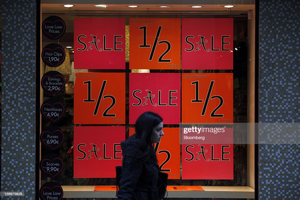 A pedestrian passes a half price sales discount advertisement in the window of a store in Athens, Greece, on Thursday, Jan. 24, 2013. Greece's government has implemented budget cuts and economic reforms to tame a fiscal deficit that has led to bailouts from the European Union and the International Monetary Fund. Photographer: Kostas Tsironis/Bloomberg via Getty Images