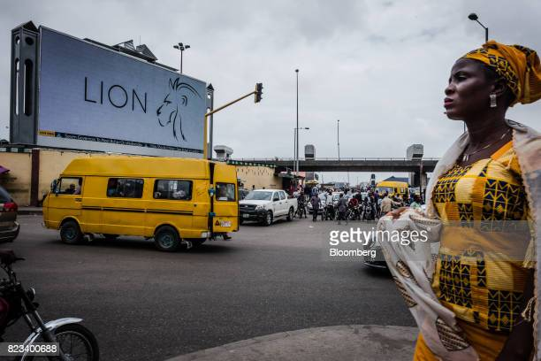 A pedestrian passes a large electronic advertising screen on a busy road in Lagos Nigeria on Wednesday July 26 2017 Nigeria's economy which in 2016...