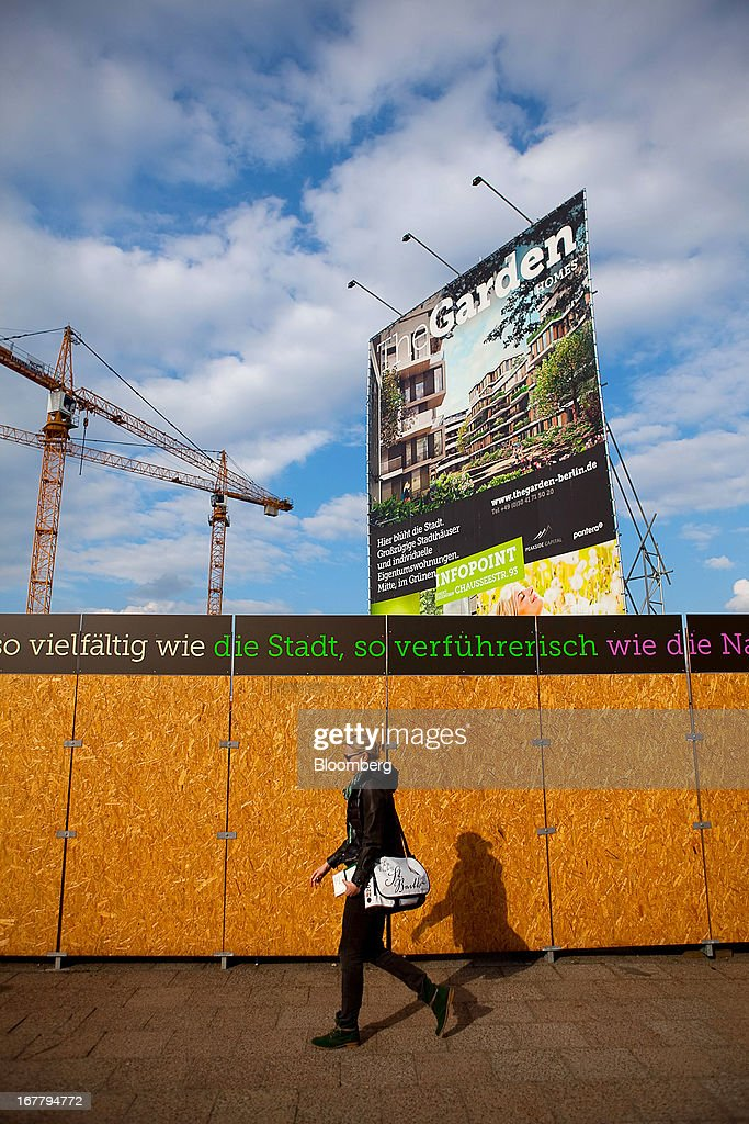 A pedestrian passes a large poster on a building site advertising new residential apartments for construction in the Mitte district of Berlin, Germany, on Monday, April 29, 2013. Rents and home prices in Germany's largest cities are rising at the fastest rate in twenty years, according to data compiled by Bulwien Gesa AG. Photographer: Krisztian Bocsi/Bloomberg via Getty Images