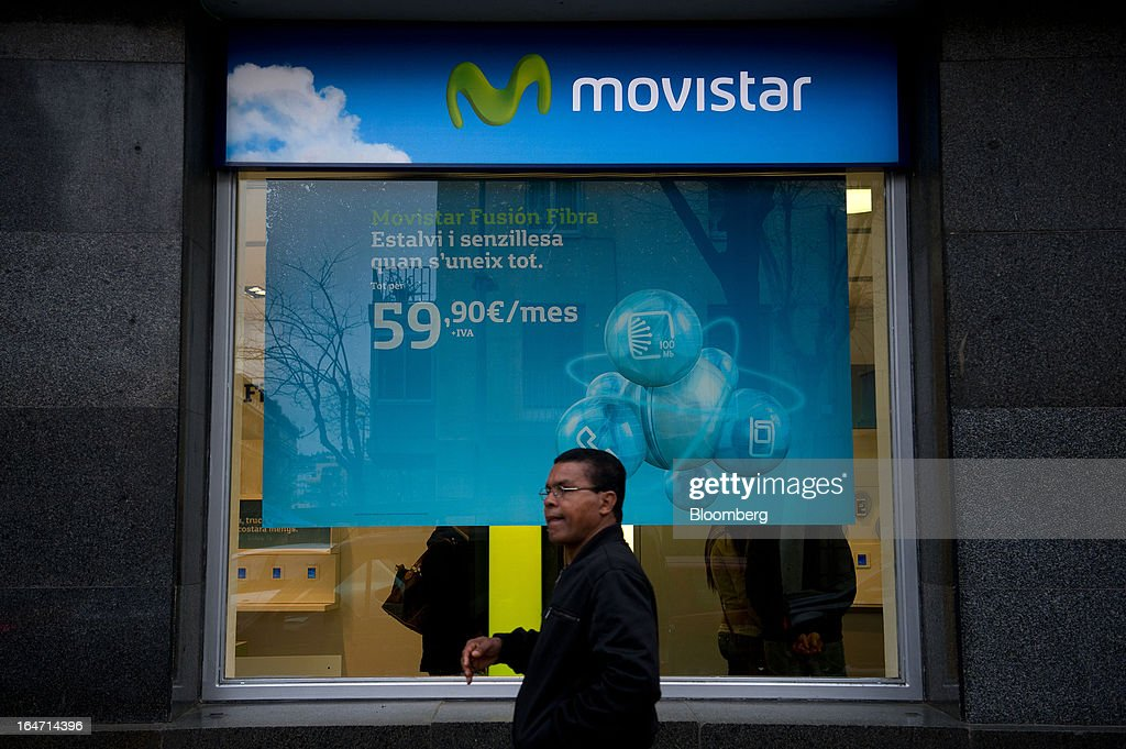 A pedestrian passes a Movistar logo above a window outside a Telefonica SA phone store in Barcelona, Spain, on Tuesday, March 26, 2013. Telefonica, seeking to reduce net debt by more than 4 billion euros this year, is following companies such as Repsol SA, Spain's biggest oil company, and builder Actividades de Construccion & Servicios SA, to sell treasury shares. Photographer: David Ramos/Bloomberg via Getty Images