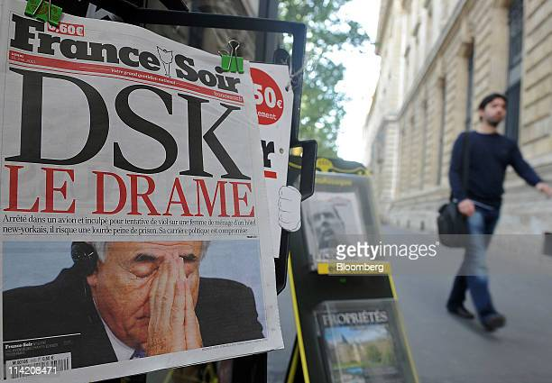 A pedestrian passes a news stand as a French newspaper hangs on display with coverage of the US arrest of Dominique StraussKahn managing director of...