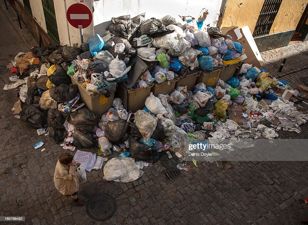 A pedestrian passes a pile of garbage during the 10th day of the Seville waste disposal strike on February 6, 2013 in Seville, Spain. Workers are striking over demands they take a 5% pay cut and extend their working week to 37.5 hours.