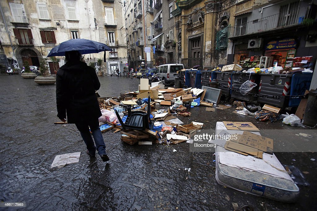 A pedestrian passes a pile of garbage strewn around trash cans outside a store in Naples, Italy, on Saturday, Feb. 1, 2014. In Naples, the local youth unemployment rate in 2012 was 53.6 percent compared to a national average of 35.3 percent. Photographer: Alessia Pierdomenico/Bloomberg via Getty Images
