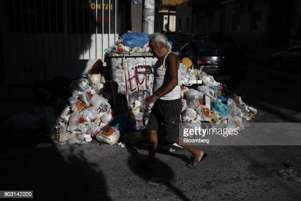 A pedestrian passes a pile of uncollected garbage in a residential district during a refuse collection strike by municipal workers in Athens Greece...