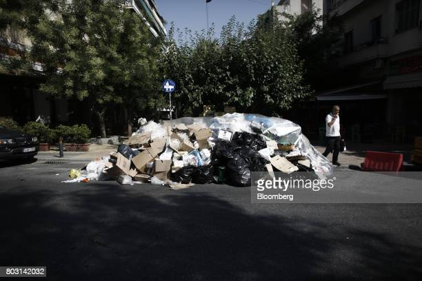 A pedestrian passes a pile of uncollected garbage on a residential road during a refuse collection strike by municipal workers in Athens Greece on...