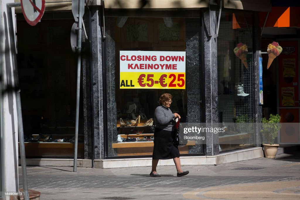 A pedestrian passes a poster advertising a 'Closing Down' sale in the window display of a footwear store on Ledra Street in Nicosia, Cyprus, on Friday, March 29, 2013. Cypriots face a second day of bank controls over their use of the euro as officials in Europe urged the country to move quickly to lift the restrictions, the first time they have been imposed on the common currency. Photographer: Simon Dawson/Bloomberg via Getty Images