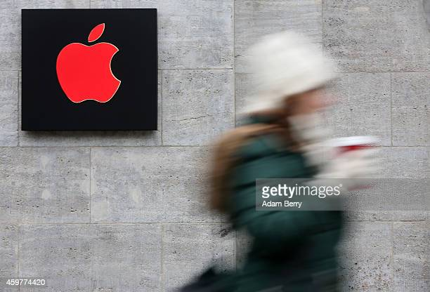 A pedestrian passes a red Apple logo at the Apple Store on December 1 2014 in Berlin Germany On World AIDS Day December 1 Apple is donating a portion...