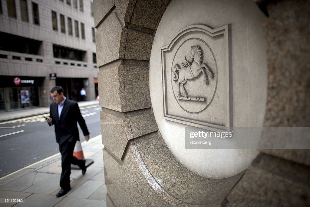 A pedestrian passes a relief in the wall of a Lloyds TSB bank branch, part of the Lloyds Banking Group Plc, in London, U.K., on Monday, Oct. 15, 2012. U.S. homeowners filed a lawsuit against 12 banks, including Lloyds Banking Group Plc, Barclays Bank Plc, and JPMorgan Chase & Co., claiming that manipulation of the benchmark Libor lending rate made their mortgage repayments more expensive. Photographer: Simon Dawson/Bloomberg via Getty Images