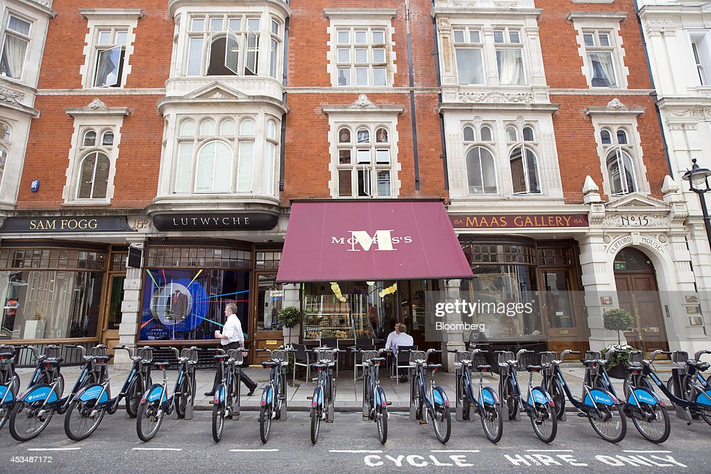 A pedestrian passes a row of Barclays Plc branded cycle-hire bicycles, parked outside commercial real estate buildings that form part of the Pollen Estate, on Clifford Street in London, U.K., on Monday, Aug. 11, 2014. Norway's sovereign wealth fund, Norges Bank Investment Management, the world's largest, bought a stake in the Pollen Estate in London's Mayfair district for 343 million pounds ($576 million), expanding its property holdings in the U.K. capital. Photographer: Jason Alden/Bloomberg via Getty Images